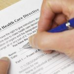 "A person filling out a form titled Advance Health Care Directive and a pen. Notes: Very shallow focus on the word 'Health"". Form created for photo using text in public domain."