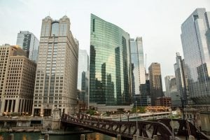 Photo of five large office buildings in Chicago with the skyline reflected in the glass of the center building, on a cloudy day