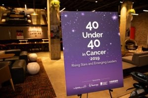 "Photo inside dimly lit conference room, with purple poster stating ""40 under 40 in Cancer"" in foreground"