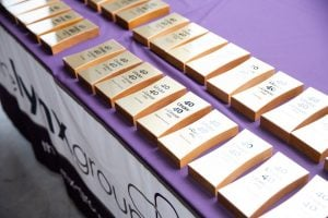 Photo: Two rows of gold-tone awards, with text, lying face-up on a purple tablecloth
