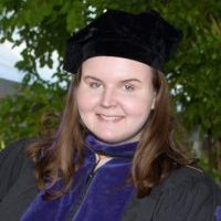 A young woman with light skin and warm brown hair smiles at the camera, wearing a cap and gown.