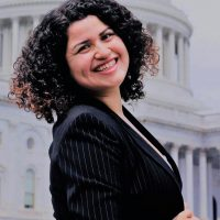 Erika Cervantes faces the camera, with her shoulders angled away from the camera, in a dark striped blazer, with short dark curly hair, in front of a white government building with visible pillars
