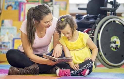 Caregiver Reading a Book with a Mentally Disabled Child